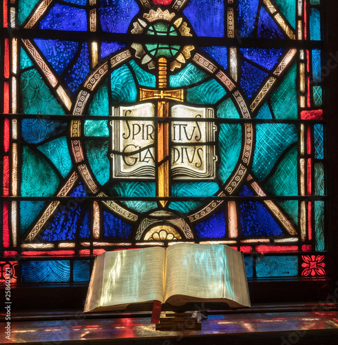 Fotografía  Colored light from stained glass window in methodist church falls across open bi