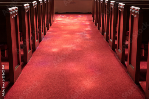 Cuadros en Lienzo  Red carpeted church aisle between pews illuminated by light from stained glass w