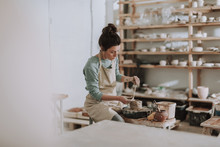 Female Ceramic Artist In Apron Working In Pottery Workshop