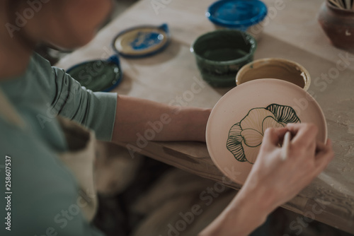 Foto auf Leinwand Akt Young lady painting ceramic plate at workshop