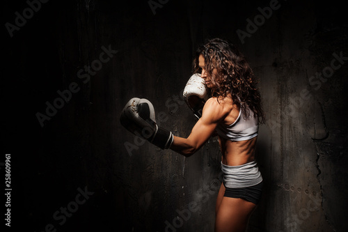 Valokuva Sport young woman wearing boxing gloves posing in combat stance