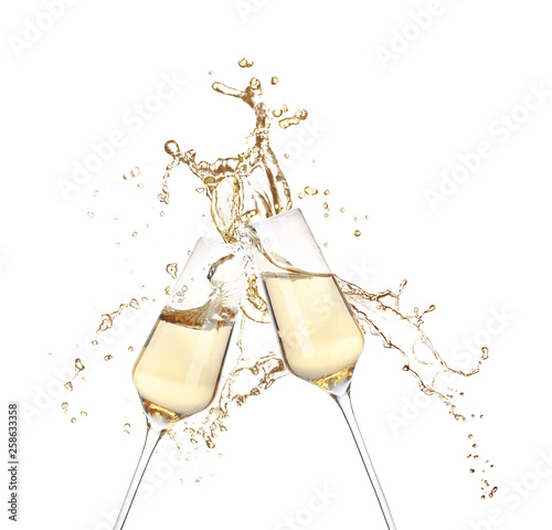 Glasses of champagne clinking together and splashing on white background Fototapeta