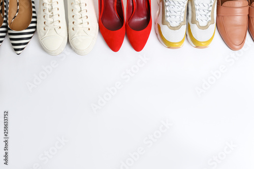 Fotografia  Different shoes on white background, top view
