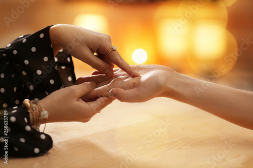 Chiromancer reading lines on woman's palm at table, closeup