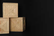 Wooden Crates On Black Background, Space For Text. Shipping Containers