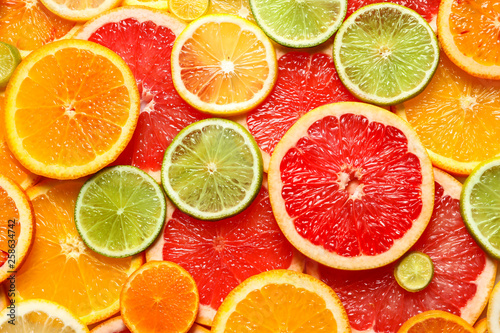 Slices of fresh citrus fruits as background, top view
