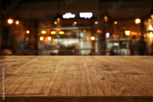 Image of wooden table in front of abstract blurred restaurant lights background Slika na platnu