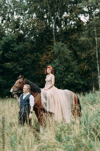 Poster de jardin Vache Wedding walk on a horse. Couple walking in nature in the forest.