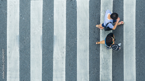 Fotografering the top view of couple people walk across the pedestrian crosswalk in white and
