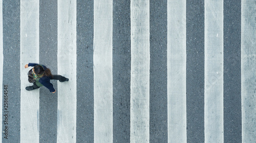 Tableau sur Toile the top view of person walk across the pedestrian crosswalk in white and grey pa