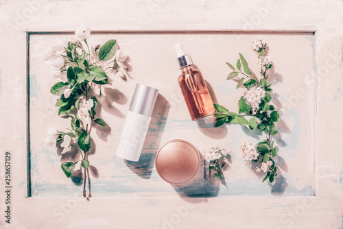 Obraz Natural organic cosmetics: serum, cream, mask on wooden background with flowers. Skincare concept - fototapety do salonu