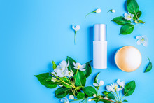 Natural Organic Cosmetics On Blue Background In A Frame Of Flowers, Blossoming Apple Tree.