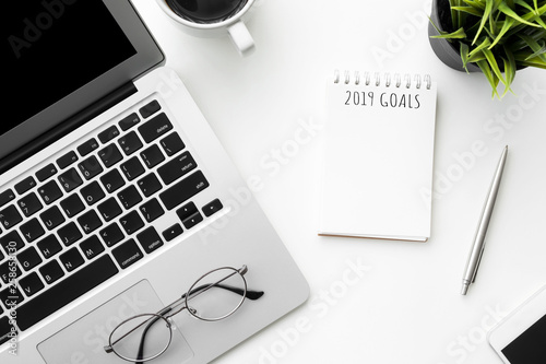 Photo  Small notebook with 2019 goals text is on top of white office desk table with laptop computer and supplies