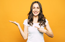 Near At Hand. Happy Girl With Wide Smile In Front Of Orange Background Is Raising Her One Hand Up And Pointing On It With The Help Of Another  Hand And A Finger.