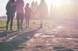 People walking through a park facing the sun