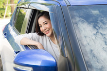 Young Asian Woman Driving A Car And Smile Happily With Glad Positive Expression During The Drive To Travel Journey, People Enjoy Laughing Transport And Rent A Car From A Car Rental Company