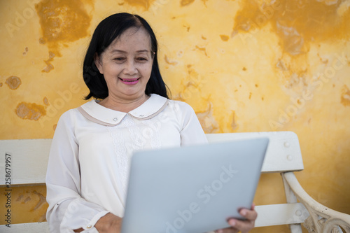Photographie  happy retirement for women Thailand and laptop holding on hands are checking the