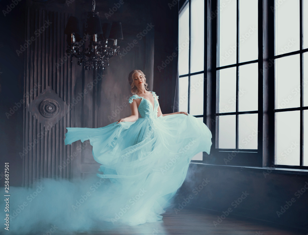 Fototapeta The magical transformation of Cinderella into a beautiful princess in a luxurious dress. Young women are blonde, spinning and dancing in a dark, gloomy room, the dress fluttering on the fly. Art photo