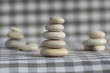 Harmony and balance, cairns, simple poise stones on white gray checkered background, rock zen sculpture, five white pebbles