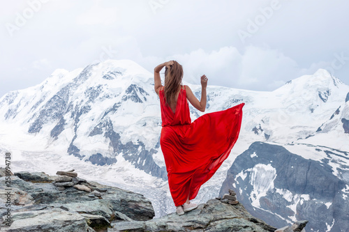 Obraz woman in long red dress on background of glacier - fototapety do salonu