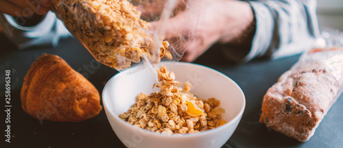 Carta da parati young man cooking breakfast and pour dry cereal in bowl