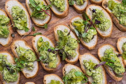 Healthy vegetarian and vegan buffet concept nutritious snack platter crispy bread slices with avocado and fresh sprouts on wooden board