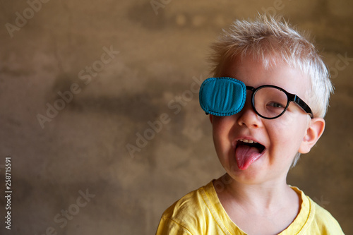 Portrait of funny child in new glasses with patch for correcting squint Fototapet