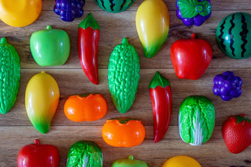 Fototapeta na wymiar Fruits and vegetables toys on wooden background.
