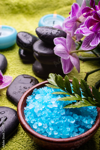 Obraz na plátně  bowl with lavender-scented bath salt, orchid, massage stones, covered with water drops, and scented candles