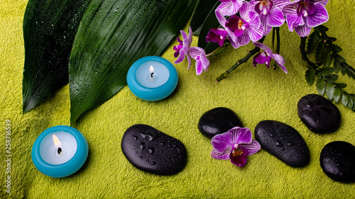 Fotografie, Obraz  scented candles, orchid and stones for massage covered with water drops on the g