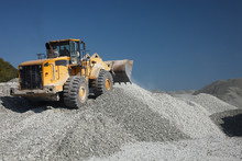 Heavy Wheel Loader Excavator Against The Background Of Gravel Hills And Blue Sky. Quarry Equipment. Mining Industry.