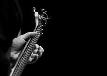 The Hand Of A Musician Playing A Guitar On A Black Background In Black And White
