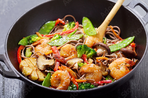 Photo Stir fried noodles with shrimps and vegetables in a wok