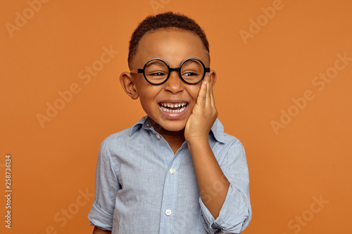 Fotografija Emotional black dark-skinned little boy grimacing and holding hand on his cheek because of intolerable toothache