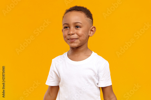 Fototapeta People, childhood, joy and happiness concept. Joyful cheerful Afro American boy of school age having fun, being in good mood, playing after he did his homework, posing isolated at yellow wall obraz na płótnie