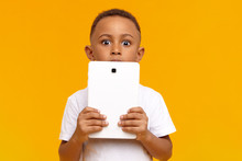 People, Children, Modern Lifestyle, Technology And Communication Concept. Emotional Bug Eyed Dark Skinned Schoolboy Holding Digital Tablet At His Face, Staring At Camera With Astonished Look