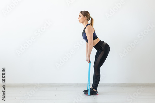 Photo  People, sport and fitness concept - young woman training with workout band in gy