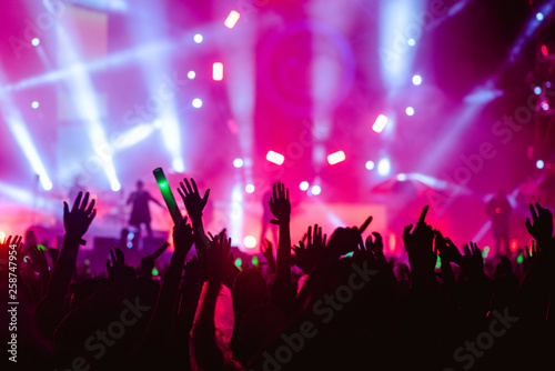 silhouettes of hand in concert.Light from the stage. - 258747954