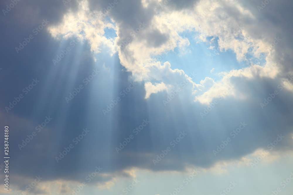 Fototapeta Ray of sun light shine through the gap among cloud with blue sky