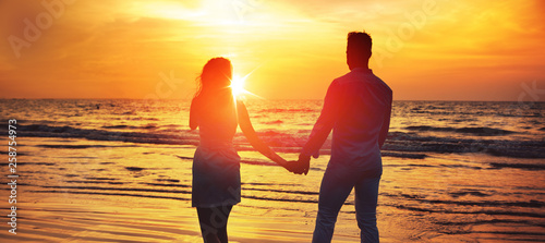 Fototapeta Young couple looking at the romantic, tropical sunset obraz na płótnie
