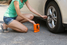 Woman Checking Air Tyre Pressure With Air Pressure Guage
