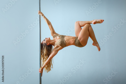 Obraz na plátne Young slim sexy blond woman in beige dress pole dancing against the background of the wall