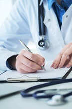 Female Doctor Filling Up Prescription Form Or Patient History List At Clipboard Pad During Physical Exam Or Disease Prevention While Sitting At The Desk In Hospital Closeup.