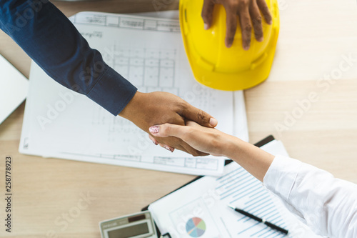 Valokuva  Successful deal, male architect shaking hands with client in construction site after confirm blueprint for renovate building