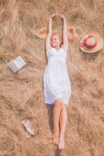Summer Vacation And Holiday Concept. Young Beautiful Blonde Woman Lies In A Golden Summer Field On Dry Grass With Book. Top View.