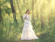 Charming Beauty With Dark Hair Standing In Light Forest, Goddess And Fairy Of Morning Sun In Warm Rays, Sweet Girl In Long White Vintage Dress With Laces Floral Patterns, Tenderness And Innocence