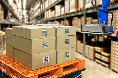 Smart logistic industry 4.0 , QR Codes Asset warehouse and inventory management supply chain technology concept. Group of boxes and Automation robot arm machine in storehouse