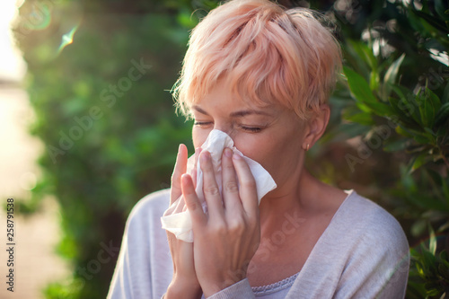 Fotografia, Obraz  Young woman with short hair sneezing into tissue
