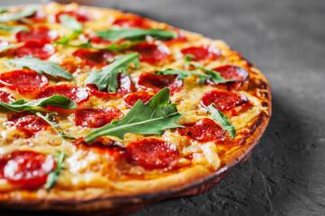 Pizza Pepperoni z Mozzarellą, salami, Pomidorami, Papryką, Przyprawami i Świeżą Rukolą. Włoska pizza na ciemnoszarym czerni łupku tle