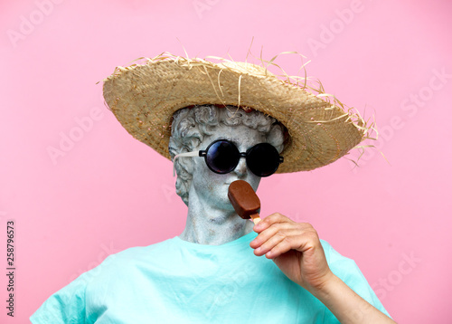 Antique bust of male in hat with ice-cream on pink background. Fotobehang